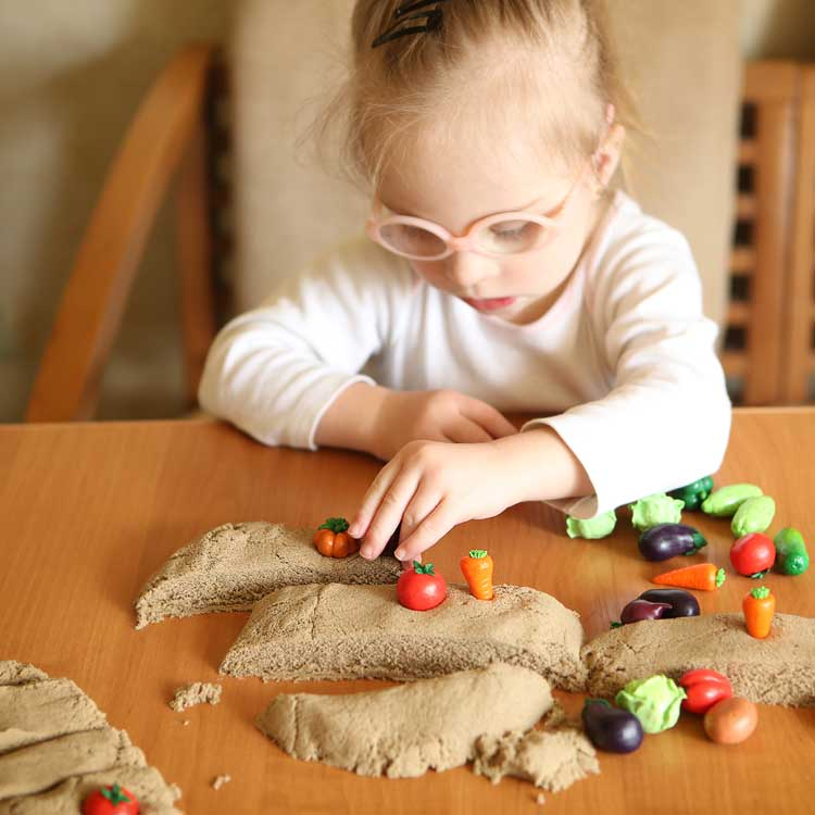 Little Downs Syndrome girl playing with kinetic sand.