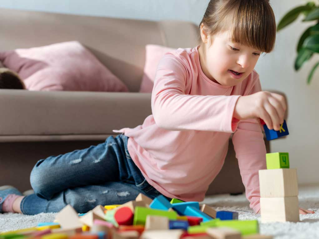 Downs syndrome girl playing with blocks.