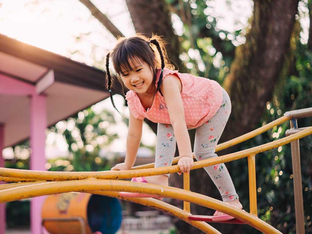 Little girl climbing on a climbing frame.